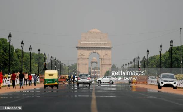 Vehicles drive along Rajpath leading to India Gate during a hot day in India's captial New Delhi on May 1 2019