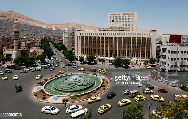 Vehicles drive along the roundabout past the Central bank of Syria in the capital Damascus' Sabaa Bahrat Square on June 17, 2020.