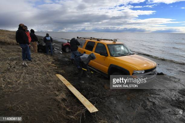 Vehicles drive beside the melting permafrost tundra on the edge of the Bering Sea at the town of Quinhagak on the Yukon Delta in Alaska on April 12,...