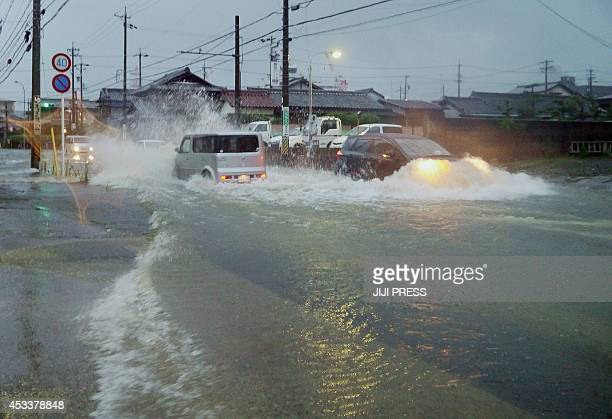 Vehicles drive down a flooded road in the city of Tsu, Mie prefecture as Typhoon Halong brings rain on August 9, 2014. The strong typhoon lashed...