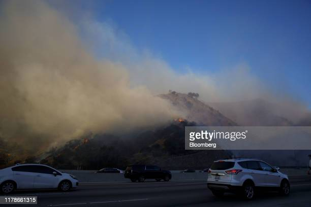 Vehicles drive in traffic on the 405 freeway through the Sepulveda Pass during a brush fire in Los Angeles, California, U.S., on Monday, Oct. 28,...