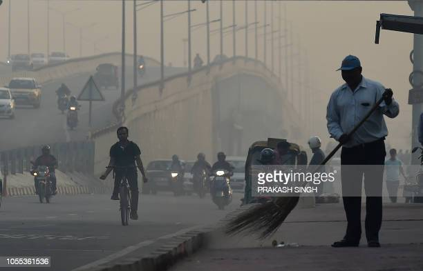 Vehicles drive on a road amid heavy smog conditions in New Delhi on October 30 2018 Smog levels spike during winter in Delhi when air quality often...