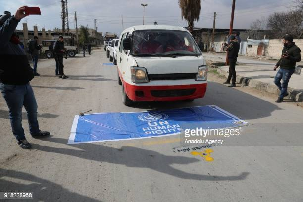 Vehicles drive over a banner reading 'UN Human Rights' as Syrians wearing gas masks hold banners during a protest against United Nations in accuse of...