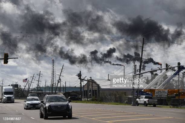 Vehicles drive past a petrol chemical plant near Highway 61 in Norco, Louisiana, on August 30, 2021 after Hurricane Ida made landfall. - Powerful...