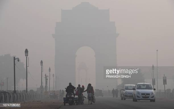 Vehicles drive past India Gate amidst a dense fog in New Delhi on December 24 2018