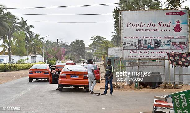 Vehicles drive past the street leading to the hotel Etoile du Sud in Grand Bassam some 40 kms east of Abidjan on March 14 a day after gunmen attacked...