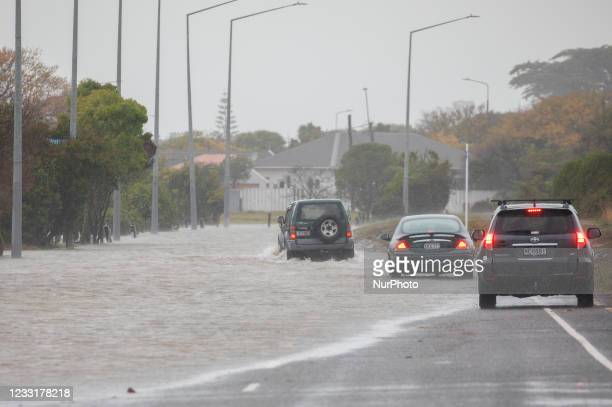 Vehicles drive through flood waters in Christchurch, NewZealand on May 30, 2021.MetService has put in place code red severe weather warning for the...