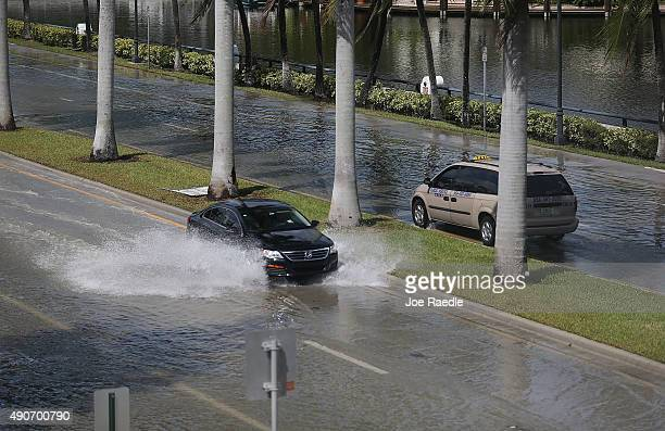 Vehicles drive through flooded streets caused by the combination of the lunar orbit which caused seasonal high tides and what many believe is the...