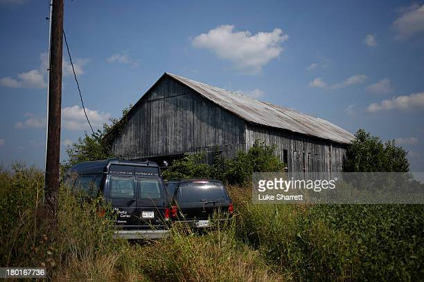 Vehicles driven by migrant workers from Mexico and Nicaragua are seen parked outside a tobacco barn September 9 2013 in Pleasureville Kentucky The...