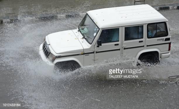 Vehicles drives through a flooded road during a heavy rainfall in Srinagar on August 7, 2018.