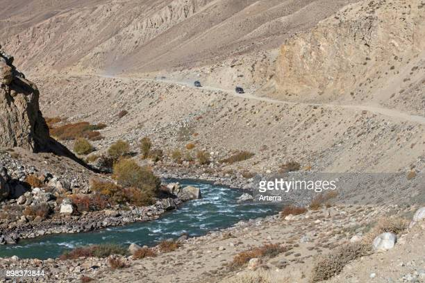 4WD vehicles driving on the Pamir Highway / M41 along the Pamir River in the GornoBadakhshan province Tajikistan