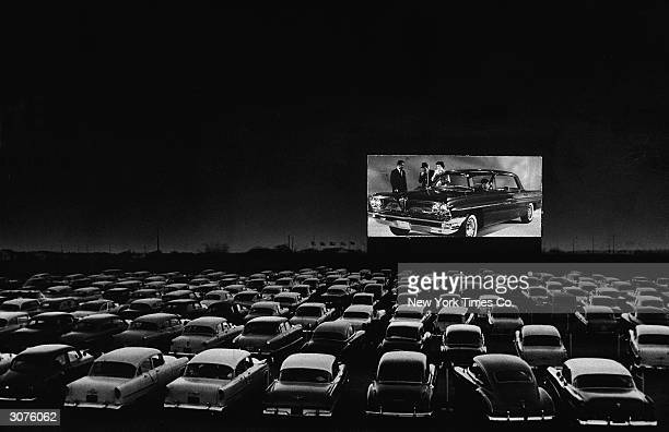 Vehicles fill a drivein theater while people on the screen stand near a new car 1950s
