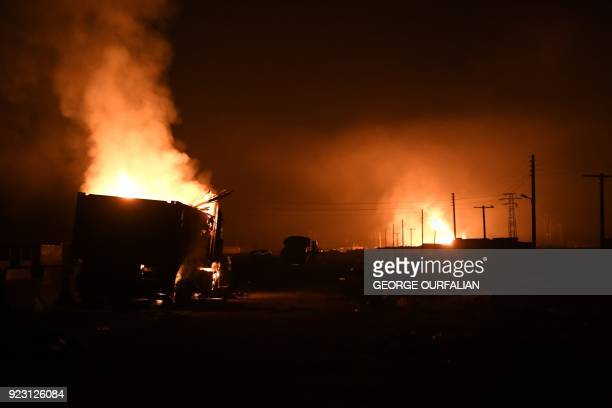 Vehicles from a convoy burn at the crossing of AlZiara in the region of Afrin northern Syria on February 22 2018 A convoy of civilian and fighters...