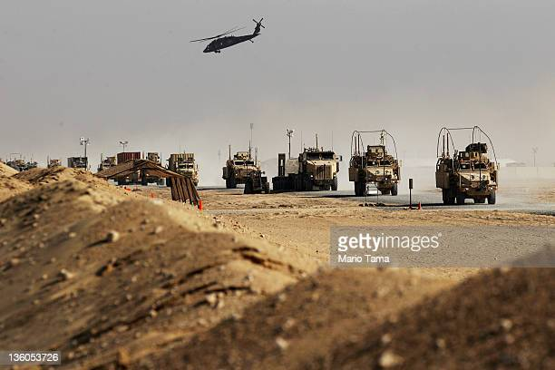 Vehicles from the last American military convoy to depart Iraq from the 3rd Brigade 1st Cavalry Division drive through Camp Virginia after crossing...