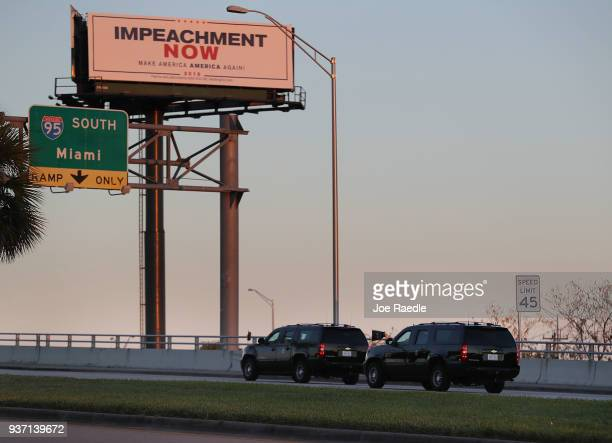 Vehicles from the motorcade carrying President Donald Trump pass a billboard reading 'Impeachment Now Make America America Again' as he is driven to...