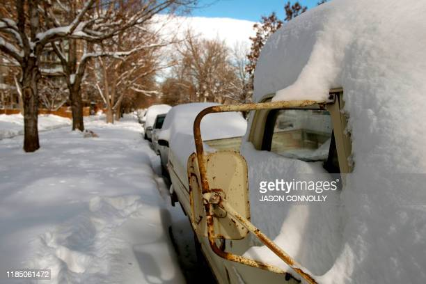 Vehicles lie buried under fresh snow in Denver Colorado on November 27 2019 A pair of storms packing heavy snow and hurricaneforce winds left tens of...