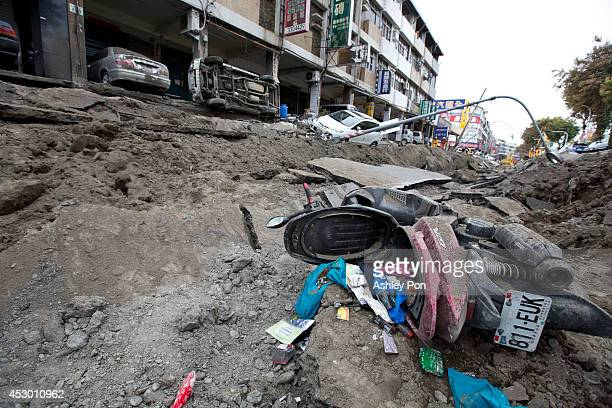 Vehicles lie on the damaged road after gas explosions in southern Kaohsiung on August 1, 2014 in Kaohsiung, Taiwan. A series of powerful gas blasts...