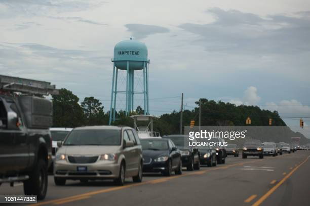 Vehicles line up along State Route 17 as people evacuate the coast of North Carolina on September 11 2018 in Hampstead North Carolina before the...