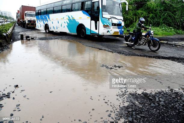Vehicles make their way on potholes ridden road on July 11 2018 in Mumbai India Heavy rains made a comeback in Mumbai causing waterlogging in many...