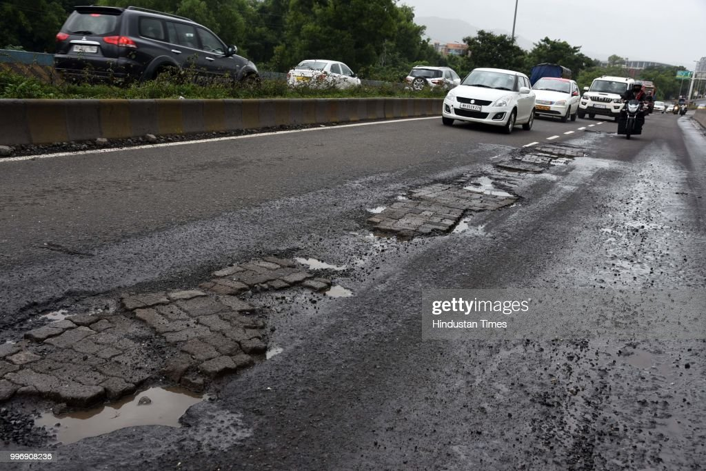Vehicles make their way on potholes ridden road, on July 11, 2018 in Mumbai, India. Heavy rains made a comeback in Mumbai causing waterlogging in many parts of the city leading to disruptions in traffic services and affected local train services. The India Meteorological Departments (IMD) Mumbai office has said heavy rainfall will continue in some parts of the city and its suburbs after similar conditions over the weekend.