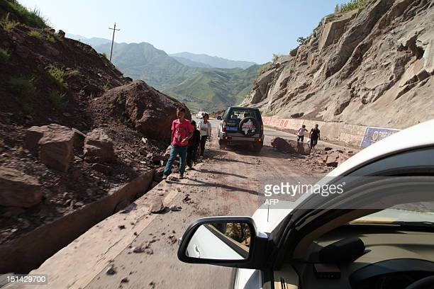 Vehicles make their way slowly along the road after a rock-fall in Yiliang, southwest China's Yunnan province on September 7 following two shallow...