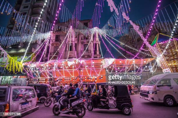 Vehicles, motorcycles, and tuk-tuks drive past a stall selling Ramadan lanterns along a main street in the in the northern suburb of Shubra of...