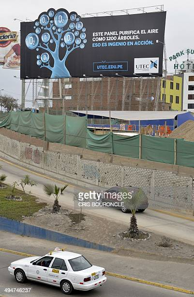 Vehicles move along a freeway in Lima on May 30 2014 by a billboard that filters pollution from the air and is capable of purifying air at a rate of...