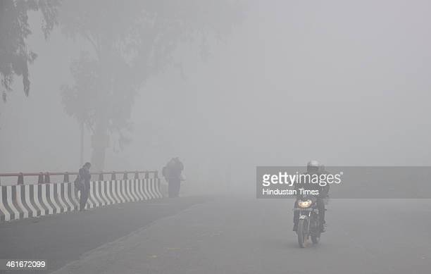 Vehicles move as heavy fog engulfed Ghaziabad and surrounding area which led to disruptions in traffic over NH24 area near Dasna on January 10 2014...