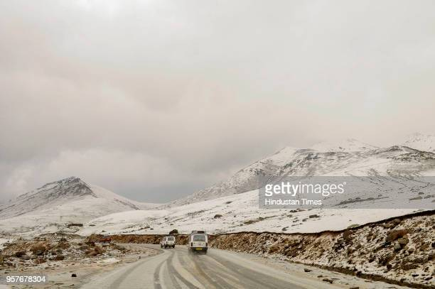 Vehicles move cautiously on a road covered with hailstones on Mughal Road near Peer ki Gali some 90 kms south of Srinagar on May 12 2018 in Srinagar...