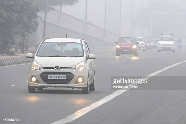 Vehicles moving during a cold and foggy morning on December 18 2014 in New Delhi India Fog and mist continued to affect normal life and vehicular...