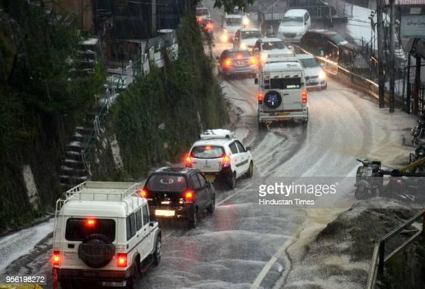 Vehicles moving slowly on the roads during hail storm at Lakkar Bazaaron May 8 2018 in Shimla India Dust storms rain and thunder lashed out in parts...
