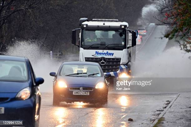Vehicles negotiate flooding on the Inverkeithing to Aberdour road as overnight snow gave way to heavy rain, on December 4 in Dalgety Bay, Scotland.