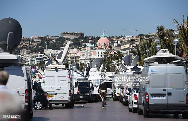Vehicles of media are parked near the Negresco Hotel in Nice on July 16 following a deadly attack on the Promenade des Anglais seafront which killed...