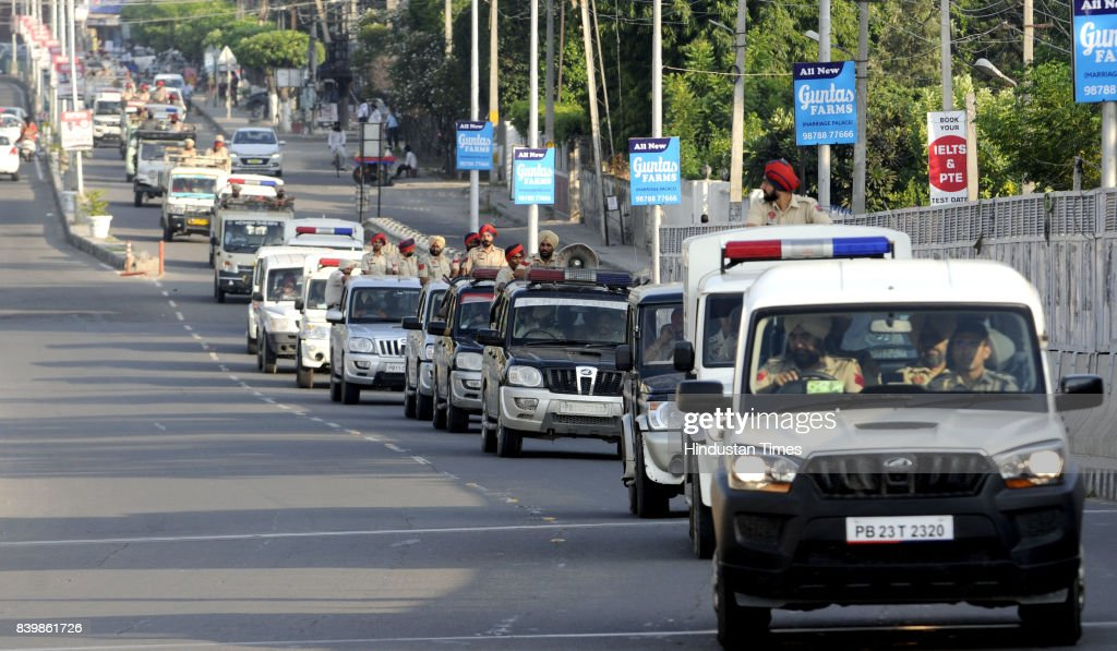 Vehicles of Punjab Police force stage a flag march through the streets after the violence on August 27 2017 in Patiala India Violent clashes across...