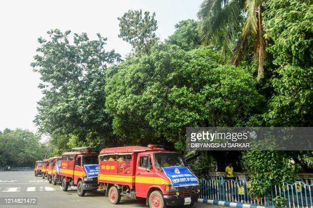 Vehicles of the Fire and Disaster Service of the neighbouring state of Odisha are parked as the personnel work for the cleaning operation in the area...