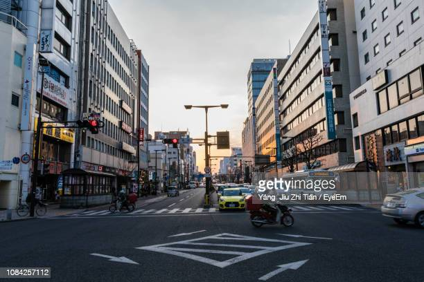 vehicles on city street against clear sky during sunset - 宇都宮市 ストックフォトと画像