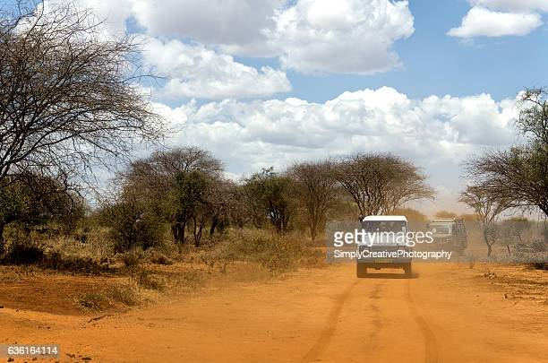 vehicles on dusty road in africa - humanitarian aid stock pictures, royalty-free photos & images