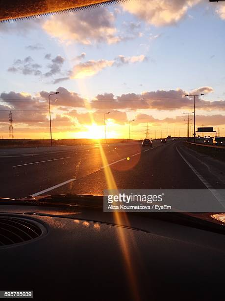 Vehicles On Highway Against Sunset Sky Seen From Car Windshield