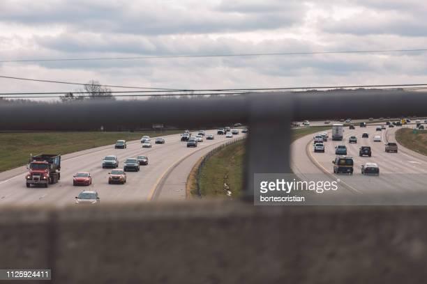 vehicles on road against cloudy sky - bortes stockfoto's en -beelden