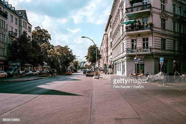 vehicles on road along buildings - stadsstraat stockfoto's en -beelden