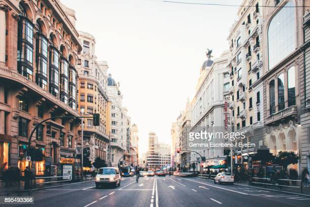 vehicles on road along buildings - madrid foto e immagini stock
