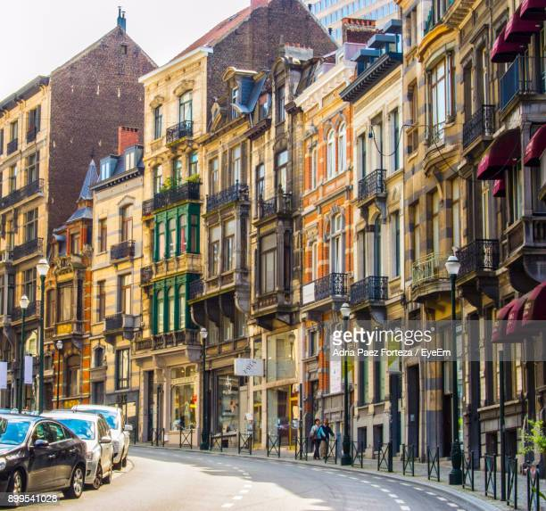 vehicles on road along buildings - brussels capital region stock pictures, royalty-free photos & images