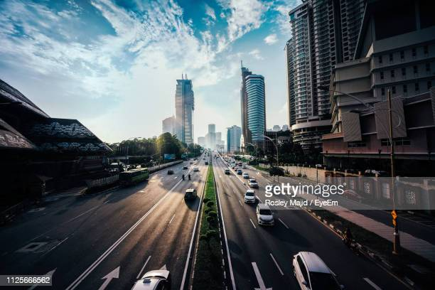 vehicles on road amidst buildings in city against sky - kuala lumpur stock pictures, royalty-free photos & images