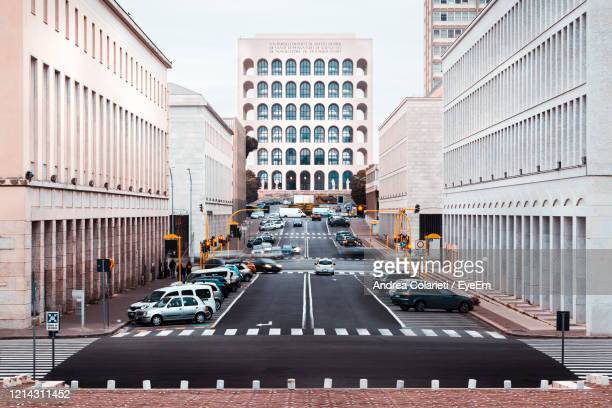 vehicles on road amidst buildings in city - eur rome stock pictures, royalty-free photos & images