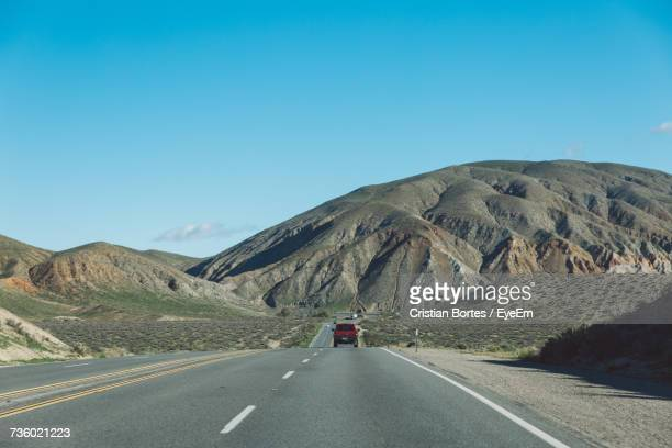 vehicles on road by mountain against clear blue sky - bortes stockfoto's en -beelden