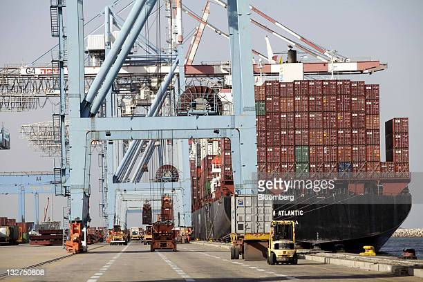 Vehicles operate beside the Zim Atlantic cargo ship laden with Zimbranded shipping containers at the Port of Haifa in Haifa Israel on Sunday Nov 13...