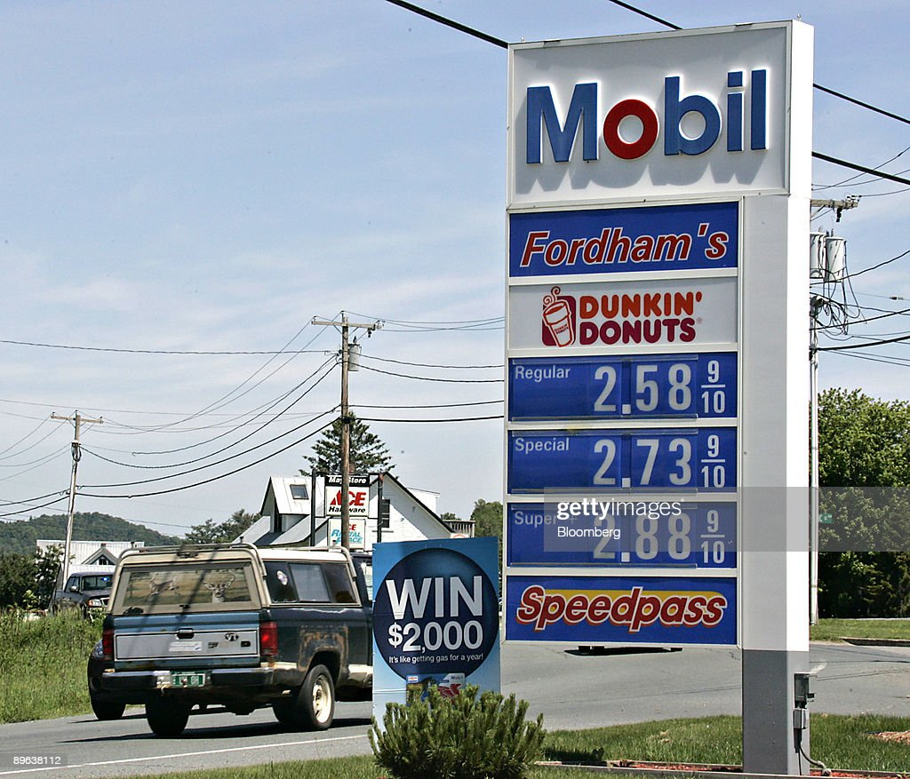 Vehicles pass a display of gas prices at an Exxon Mobil gas