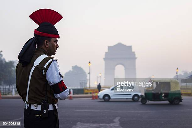 Vehicles pass a police officer at the India Gate monument shrouded in smog in New Delhi India on Monday Jan 11 2016 A 2judge Delhi High Court panel...