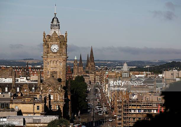 Vehicles pass along Princes Street as the clock tower of Balmoral hotel is seen on the city skyline in Edinburgh UK on Wednesday July 31 2013 The...