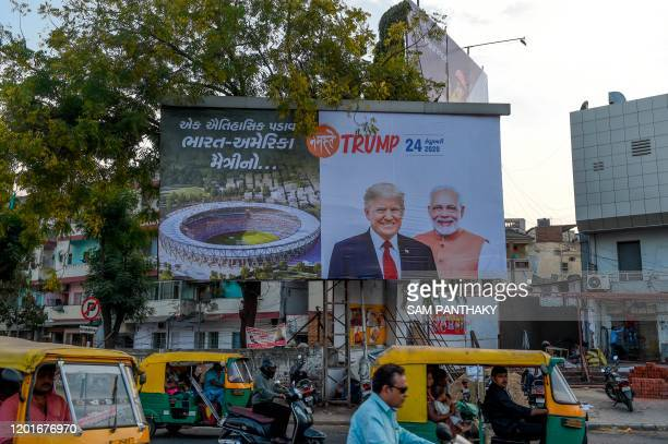 Vehicles pass below a billboard depicting US President Donald Trump who will inaugurate the Motera Cricket Stadium as the world's largest cricket...